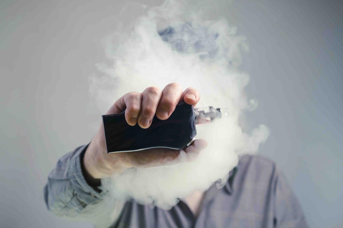 a man behind a cloud of vapor holds up an e cigarette mod image