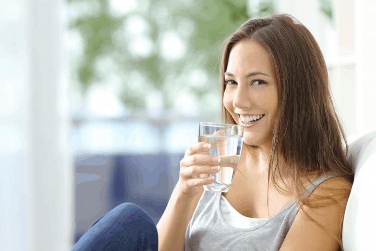 cô gái uống nước khi bị huyết áp thấp