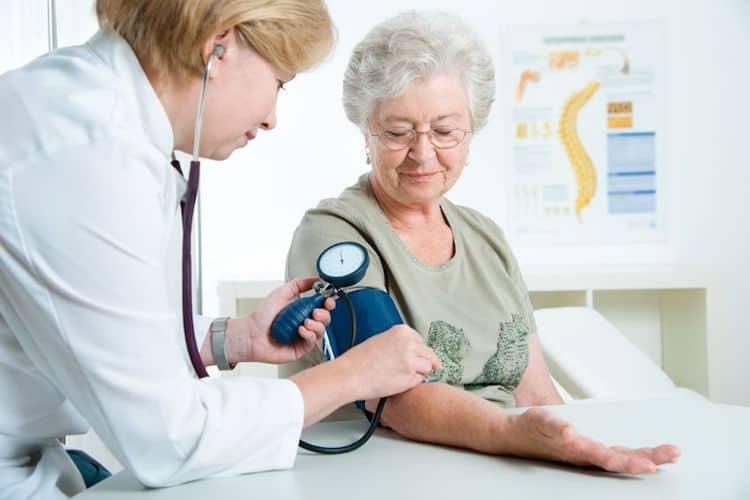 bác sĩ đo huyết áp cho người phụ nữ lớn tuổi