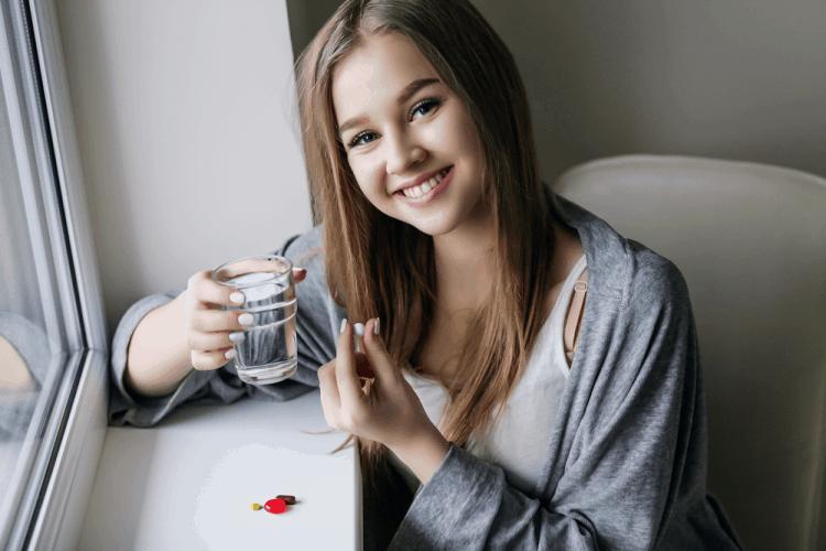 cô gái đang uống thuốc điều trị huyết áp thấp